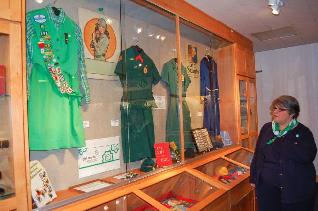 Uniforms displayed are a Cadette/Senior Scout uniform from 1980, Senior Wing Scout from 1960, Senior Girl Scout from 1948, and a Mariner Girl Scout uniform from 1934,