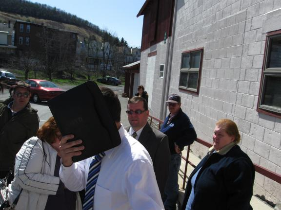 KATHY KUNKEL/TIMES NEWS Jonathan Paul Williams, a contractor from North Wales, hides his face as he runs a gauntlet of incensed homeowners who claim he defrauded them over repairs to their Tamaqua and Rush Township homes.