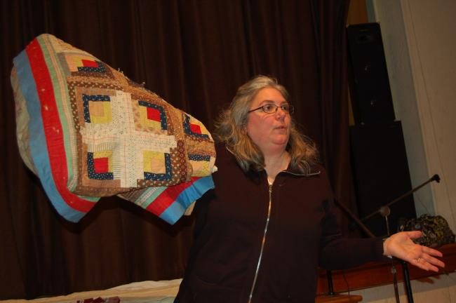 LINDA KOEHLER/TIMES NEWS At a Palmerton Concourse Club meeting, Michelle McLaughlin displays a Centennial quilt from her husband's family, dating it to 1876, determined by the fabric that has the dates 1776-1876 printed on it.