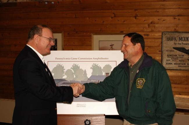 Hawk Mountain Sanctuary president Jerry Regan, left, and Pennsylvania Game Commission executive director Carl Roe have a celebratory handshake after their join announcement of plans to construct the Pennsylvania Game Commission Amphitheater at the 2…