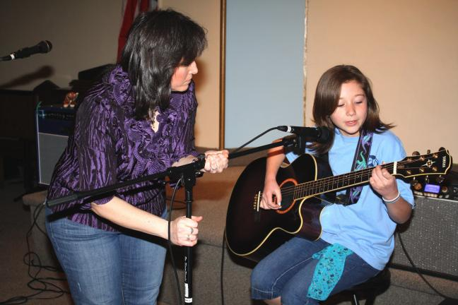 ANDREW LEIBENGUTH/TIMES NEWS Center volunteer Kathy Rimm fixes the microphone so young talent Faith Roberts, 14, of Tamaqua, can perform a vocal guitar solo.