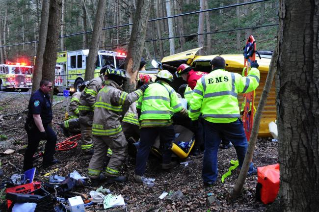 Larry Neff Franklin Township fire crewmen remove a driver from the scene of Saturday's accident along Fairyland Road.