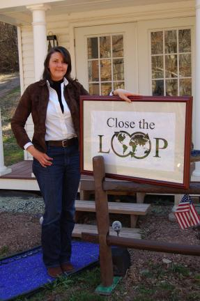 LINDA KOEHLER/TIMES NEWS Rita Lacey of Close the Loop, has been named Home-based Business Champion of the Year. She is standing on a recycled product Close the Loop promotes-tumbled glass gravel- and next to another of her products she promotes,…