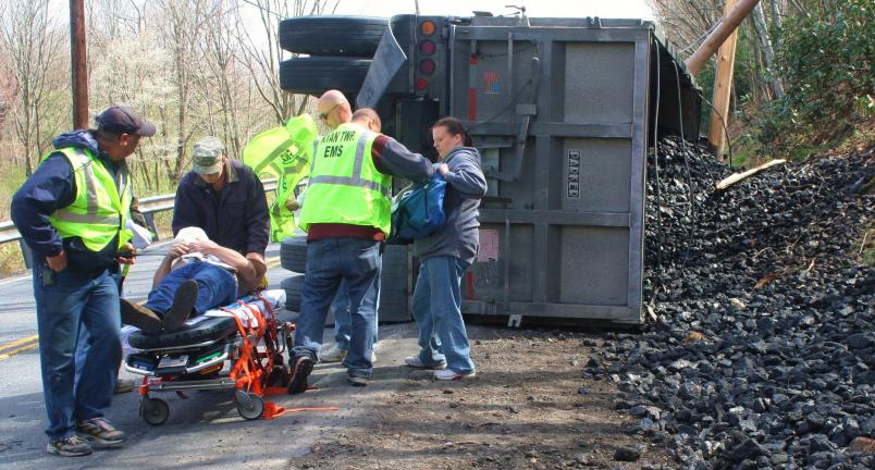 ANDREW LEIBENGUTH/TIMES NEWS Rescuers place the driver of the tractor trailer on a stretcher following Monday's accident in Barnesville.