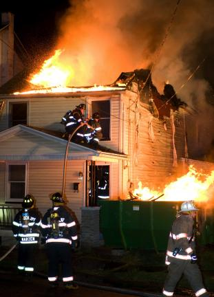 Bob Ford/TIMES NEWS Flames leap through the roof of a vacant home in Jim Thorpe last night.