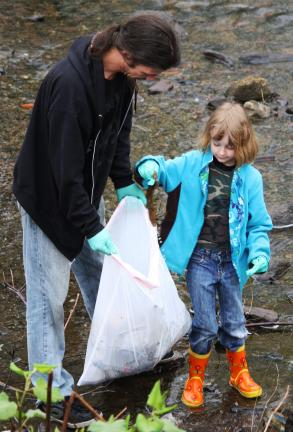 ANDREW LEIBENGUTH/TIMES NEWS Members of the community joined together with the Tamaqua Girl and Boy Scouts recently to help spruce up the area around the riverwalk in Tamaqua. Alexandria Fucci, 7, uses gloves to place trash into a garbage bag held…