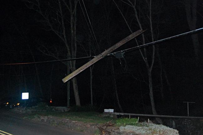 VICTOR IZZO/SPECIAL TO THE TIMES NEWS A utility pole hangs on wires on West Broadway Thursday after being struck by a vehicle driven by a Barnesville man.