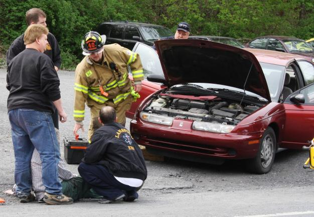 ANDREW LEIBENGUTH/TIMES NEWS Good Samaritans Michael Erbe and Ryan Woodroffe, both on left, work with paramedics and firefighters as they continue to help a Lansford man who was run over by his own car in Coaldale Wednesday. Erbe and Woodroffe…
