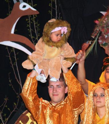 ANDREW LEIBENGUTH/TIMES NEWS Julianna Perez, 15 months, playing a baby lion, is raised in the air by Harmony Scholar performers David Aungst and Amanda Stocker during their finalee performance of Lion King.