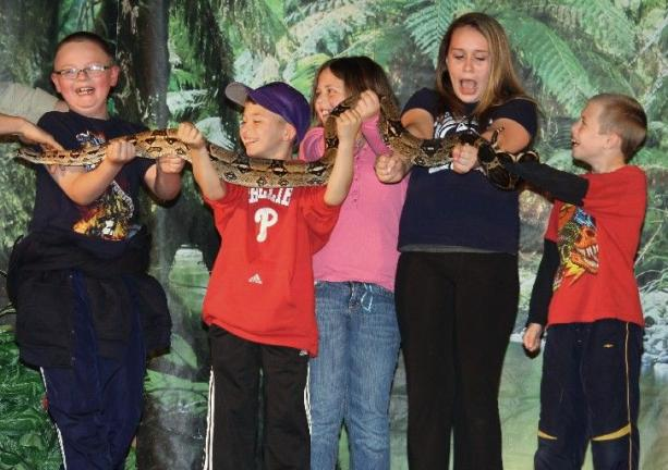 ANDREW LEIBENGUTH/TIMES NEWS Above, holding a large snake during the Tamaqua show are, from left, Shane Vengen, 8; Caleb Monk, 9; Emily Zuber, 10; Savannah Adams, 11; and Thomas Case, 8.