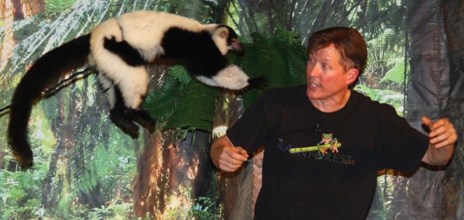 ANDREW LEIBENGUTH/TIMES NEWS Show director Mike Kohlrieser looks up as a black and white lemur jumps on his shoulders.