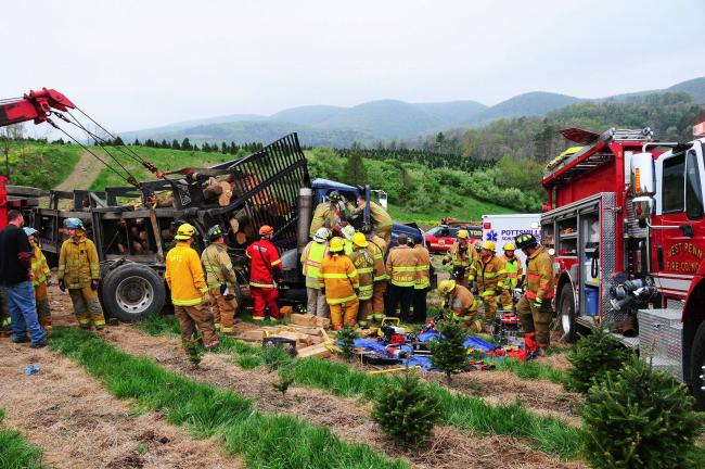 Larry Neff/special to the times news Fire company personnel free a tractor trailor driver who was trapped in his rig after logs crushed the rear of his cab.