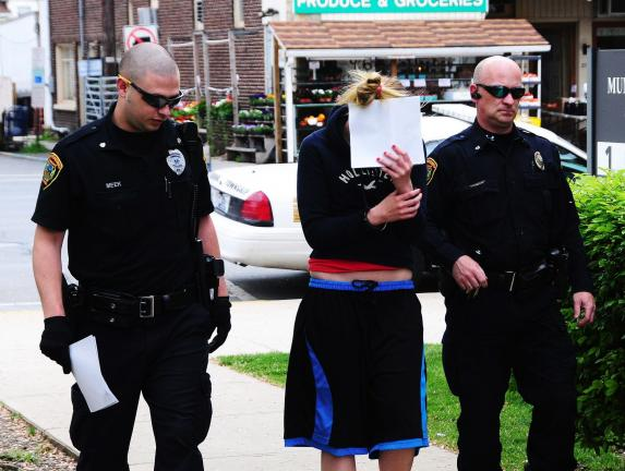 Larry Neff/special to the times news Mahoning township police officers Tyler Meek and Jeff Frace lead Holly Koch into the office of District Justice Edward Lewis for her arraignment on a multitude of burglary charges.