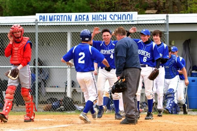 MIKE FEIFEL/TIMES NEWS Palmerton's Lee Kuntz is congratulate by teammates Cody Geist and Brett Snyder as he scores the winning run on a bases loaded hit by pitch in Saturday's game with Jim Thorpe.