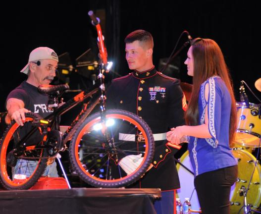 Ron Gower/TIMES NEWS Country singer Aaron Tippin, left, completes assembly of a bicycle after singing a song at Penn's Peak, Friday, while looking on are Marine Sgt. Andrew Rawcliffe of York and local country singer Nicole Donatone. At all his…