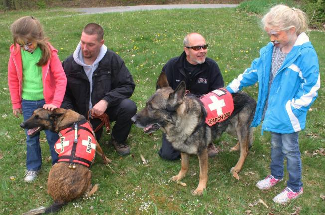 "ANDREW LEIBENGUTH/TIMES NEWS The event consisted of a visit from a search and rescue team from Consummate K-9 Training, Andreas. From left visitor Abigail Coles, 6; dog trainer Don Wilcox with ""Alex;"" training director Dave Balmat with ""Lucas;"" and…"