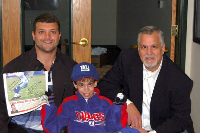 ED HEDES/TIMES NEWS New York Giants fullback Henry Hynoski (left) and ESPN football commentator Matt Millen (right) take time out at the Fifth Annual Bo Tkach Memorial Golf Tournament to sign autographs for special gust Connor Lavelle, a fan of the…