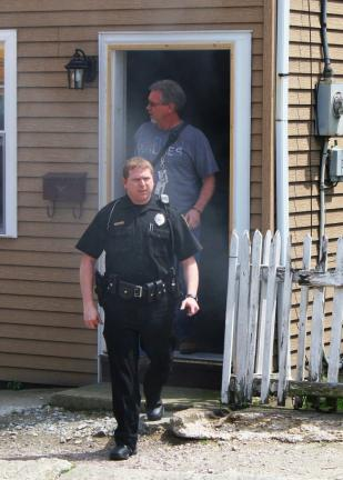 ANDREW LEIBENGUTH/TIMES NEWS In top photo Tamaqua Police officer Mike Hobbs, front, and Fire Chief Tom Hartz exit the smoke-filled home prior to the arrival of the fire trucks.
