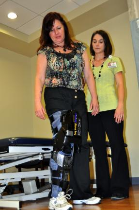 DONALD R. SERFASS/TIMES NEWS Kim Kostak, Tamaqua, takes a step using the Tibion Bionic Leg with assistance from Good Shepherd Physical Therapy's Susan Lawfer, Palmerton site manager.
