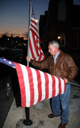 ANDREW LEIBENGUTH/TIMES NEWS FILE PHOTO Tamaqua American Legion member Ray Hughes, Tamaqua, places flags in poles in preparation' for an upcoming parade.