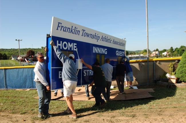 Gail Maholick/TIMES NEWS Volunteers carry a brand new scoreboard that was installed at Franklin Township Little League field at the Phifer Ice Dam Park. The scoreboard is wireless and was installed Saturday morning and put into use on Saturday.