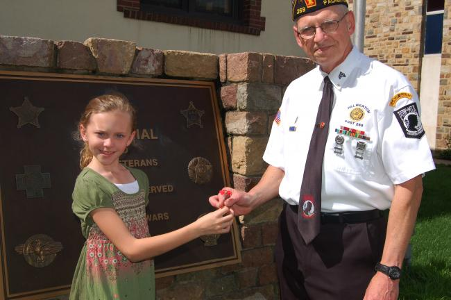 TERRY AHNER/TIMES NEWS Ella Cronk, a fourth-grade student at S.S. Palmer Elementary, who will serve as Miss Poppy for this year's Memorial Day Parade in Palmerton, presents a poppy to her grandfather, Joe Uhnak, First Vice Commander, Palmerton…
