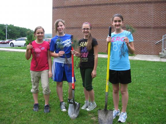 STACEY SOLT/SPECIAL TO THE TIMES NEWS ABOVE: Cadette Girl Scouts Lindsey Shimko, left, Skye Klotz, Madison Wenig, and Holly Ahner prepare to plant trees at Towamensing Elementary School. The Scouts from Palmerton Troop 37 planted trees as part of…