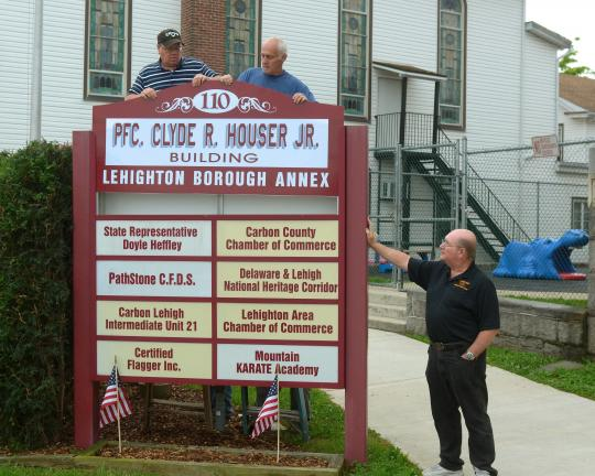 Bob Ford/TIMES NEWS Lester Miller, left, and Clark Ritter place a new sign on the Lehighton Annex building on Third Street, while Jim Walp looks on from the ground. The annex while now also be known as the Pfc. Clyde R. Houser Jr. Building.