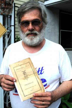 Ron Gower/TIMES NEWS Lenny McGavin of High Street, Jim Thorpe, holds program from 1922 Memorial Day Services in what was then called Mauch Chunk. He found the program behind some attic boards at his parents' house.
