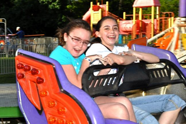 Samantha Schubert of Scranton (left) and Caitlynn Rendon of Tobyhanna ride the Sizzler at the Community Block Party at Sam Miller Field.