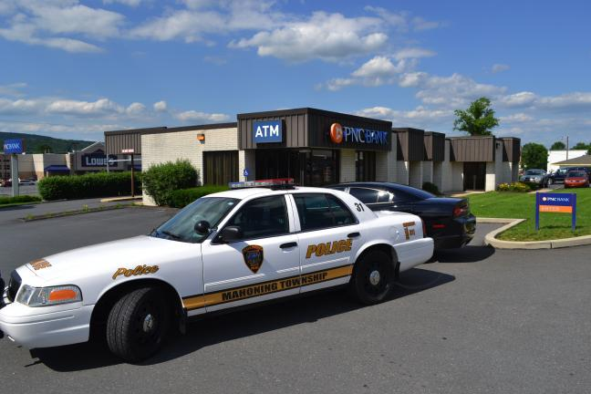 SHERI RYAN/SPECIAL TO THE TIMES NEWS Mahoning Township police cars block the entrances to the parking lot outside of the PNC Bank in Lehighton following a robbery that took place Thursday afternoon.
