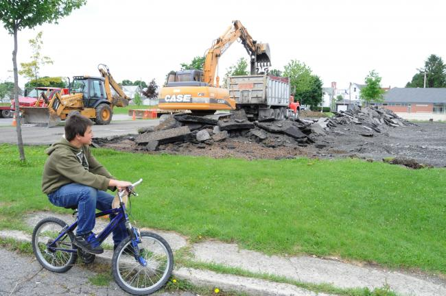 Ron Gower/TIMES NEWS Brandon Yarnal, 14, of Summit Hill, watches as heavy equipment digs up the macadem on the basketball courts along West Amidon Street in Summit Hill. The two existing courts will be replaced with two new courts that will have…