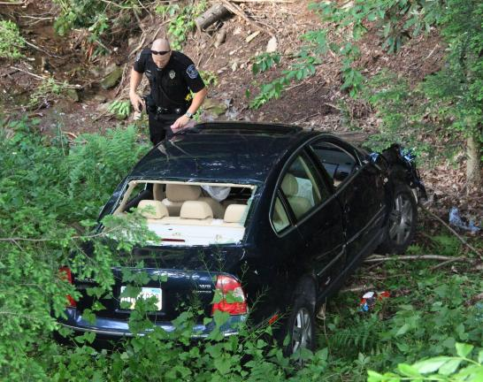 ANDREW LEIBENGUTH/TIMES NEWS Rush Township Police Officer Corey Herring inspects the car as it sits about 100 feet down the embankment.