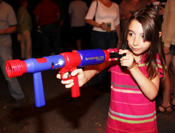 ANDREW LEIBENGUTH/TIMES NEWS Emily Hartranft, 8, takes aim with a marshmallow gun during the East End Fire Company's community block party held over the weekend.