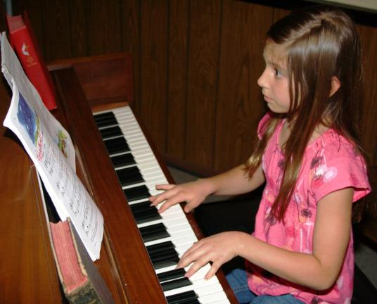ANDREW LEIBENGUTH/TIMES NEWS Sadie Morrison, 10, plays the piano during a recent open stage event at the center.