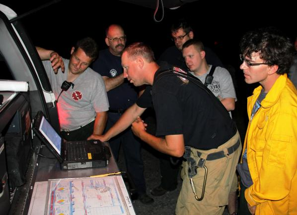 Emergency responders look over topography imagery of Lansford's mountains on a laptop in the back of the Carbon County EMA Command Unit.