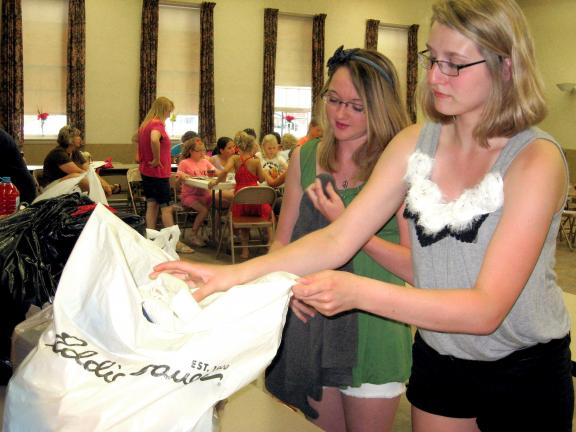 STACEY SOLT/SPECIAL TO THE TIMES NEWS Jackie Malloy, left, secretary of the Mahoning Valley 4-H Community Club, and Elyse Kistler, club vice president, organize clothing donated by club members during their June meeting. Club members aimed to donate…