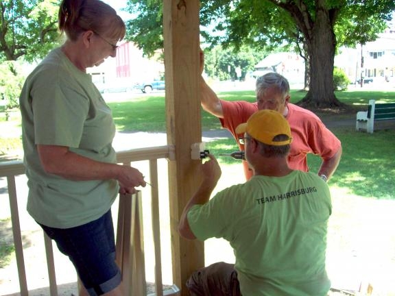 Linda Schoenberger waits to install balusters on the new railing on the gazebo. Installing supports are Weissport Mayor Jonathan Troutman, assisted by Bob Maholick.