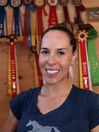 Delia Alvarez-Apollo in front of some of the ribbons that she has won. She started riding at the age of seven, became a professional equine trainer five years ago, and opened Apollo Farms Ltd. in May.