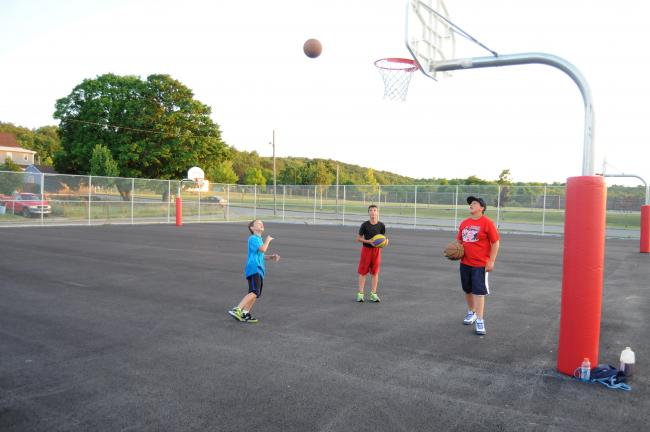 RON GOWER/TIMES NEWS Gabriel DeMatto, 9, left, takes a shot at the basket on the newly constructed basketball courts along Amidon Street in Summit Hill, while looking on are Kyle Bruno, center, age 14, and Christian Slane, 12. The new courts are…
