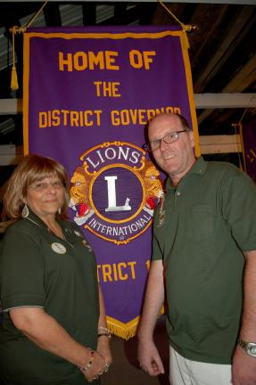 Gail Maholick/TIMES NEWS Outgoing 14-U District Governor Scott Dudley, right; presents the 14-U District Governor Banner, to incoming District Governor Angela Mimms.