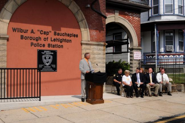 "RON GOWER/TIMES NEWS Lehighton Mayor Donald Rehrig speaks during dedication program in memory of the late Wilbur ""Cap"" Bauchspies. Seated, front l-r, are Bessie Bauchspies, the widow of the honoree; State Senator John Yudichak, State Representative…"