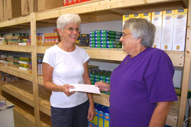 Gail Maholick/TIMES NEWS Shirley Radler, coordinator of the local Crop Walk held annually at the Lehigh Canal, Weissport, right, presents a check of $1,030.47 to Carolyn Long, Lehighton Trinity Food Bank coordinator.