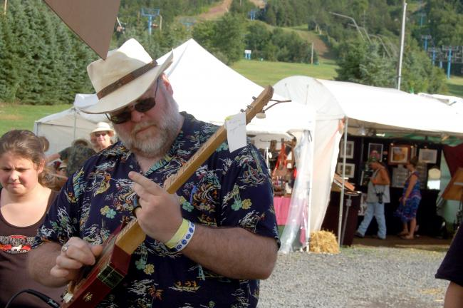 TERRY AHNER/TIMES NEWS Blues enthusiast Bill Palmieri of Connecticut, plays a cigar box guitar in front of the Victory Cigar Box Guitars vendor Sunday at the Pennsylvania Blues Festival staged at Blue Mountain Ski Area.