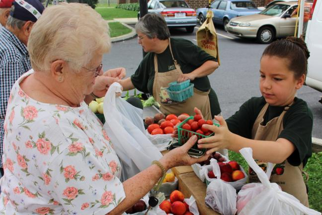 Florence Inama, Tamaqua, receives fresh fruits and vegetables from Megan Schoener, 10, of Leiby's Farm Market. Also pictured is Barb Leiby.