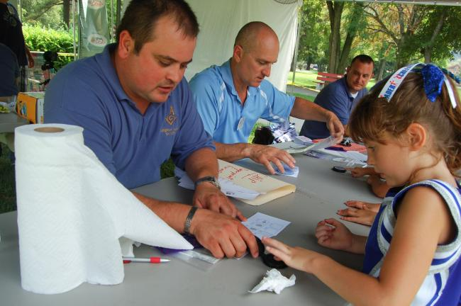 TERRY AHNER/TIMES NEWS Caroline Sterling, 7, of Palmerton, has her fingerprint taken by Pierce Wagner, of the Lehighton Legion No. 621, as part of the CHILD ID PROGRAM (CHIP), during the Kids Fair Saturday in the Palmerton Community Park. Seated…
