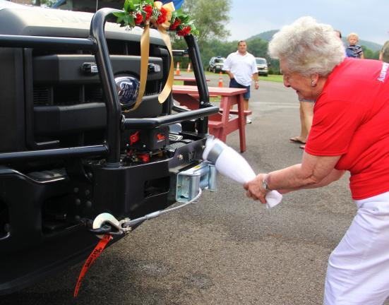ANDREW LEIBENGUTH/TIMES NEWS Taking part in the christening, Martha Raynock, 35-year volunteer with the L & L Fire Company, smashes a towel-wrapped wine bottle against the front bumper of the fire company's new 2012 Ford F150 brush truck.