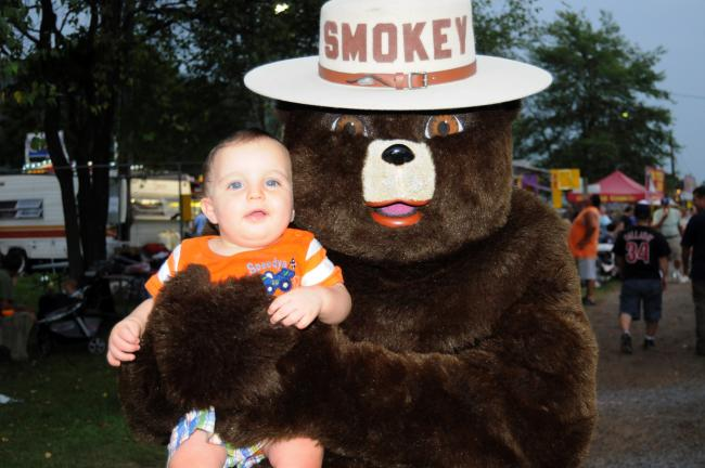 RON GOWER/TIMES NEWS Smokey Bear likely seems like a giant, live Teddy Bear to 10-month-old Darin Tyler of Palmerton, at the Carbon County Fair near Palmerton. The fair continues through Saturday.