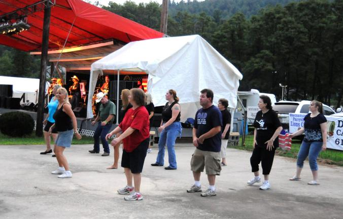 "RON GOWER/TIMES NEWS Line dancers enjoy themselves at the Carbon County Fair near Palmerton while in the background, the band Crazy Hearts performs. The fair will have a ""Country Spectacular"" featuring five bands tomorrow."