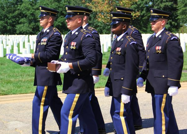 Members of the Third United States Infantry Honor Guard, carrying the cremated remains of Camerini, march in step during the cemetery procession to the grave.